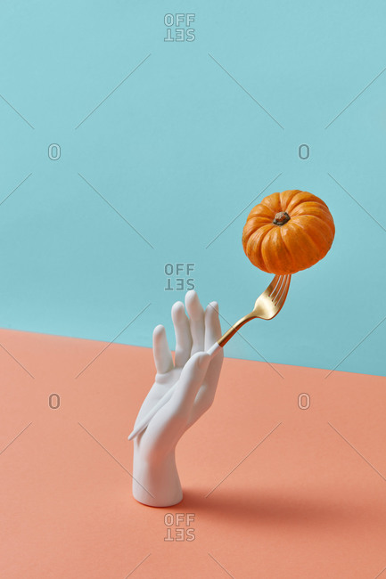 Creative dinner set - plastic mannequin hand is holding fork with ripe natural pumpkin vegetable on a duotone pastel background, copy space. Halloween concept.