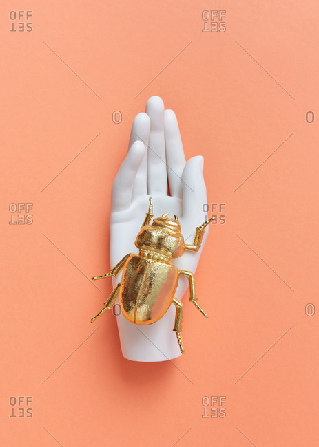 White artificial plastic mannequin hand holds golden metal beetle above pastel coral background, copy space.
