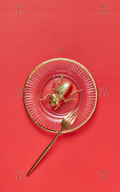 Served table setting from vintage glass plate with metal golden beetle on it and fork from gold on a coral background, copy space. Egyptian Scarab. Top view.