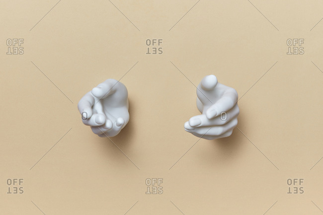 Couple plastic mannequin hands on a light beige background, copy space. Gesture of giving or receiving of something.