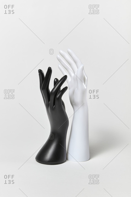 Gestures of human plastic mannequin hands raised up, black and white colors on a white background, copy space. Equality and non-discrimination of color skin and race. BLM concept.