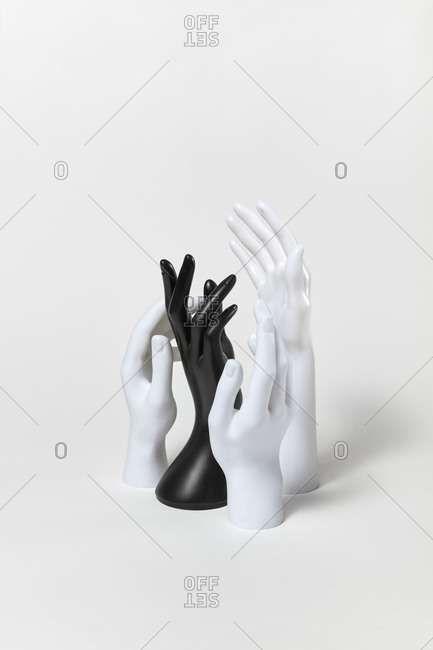 Mannequin black and white plastic hands raised up with different gestures on a white background, copy space. Equality and non-discrimination of color skin and race. BLM concept.