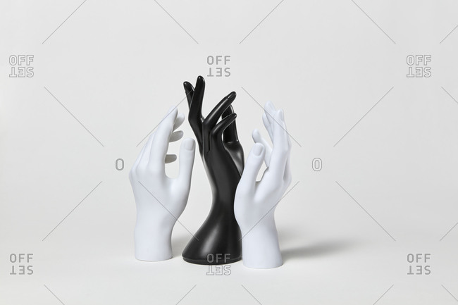 Group of black and white mannequin plastic hands raised up with gestures on a white background, copy space. Equality and non-discrimination of color skin and race. BLM concept.