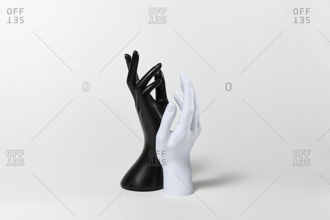 Two raised up mannequin hands white and black colors on a white background, copy space. Equality and non-discrimination of color skin and race. BLM concept.