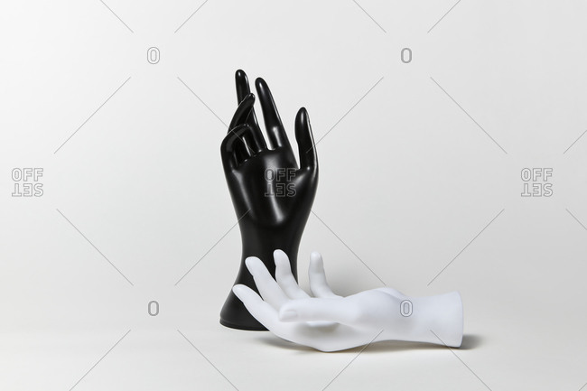 Couple of mannequin hands vertical black and horizontal white on a light grey background, copy space. Equality and non-discrimination of color skin and race. BLM concept.