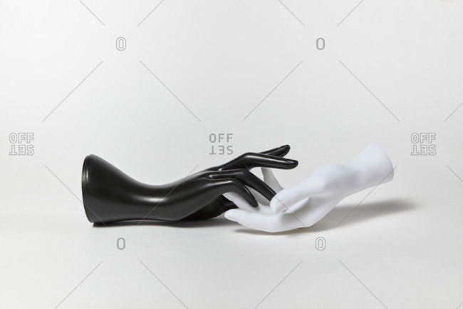 Two human plastic mannequin hands black and white colors as a symbol handshake on a white background, copy space. Equality and non-discrimination of color skin and race. BLM concept.