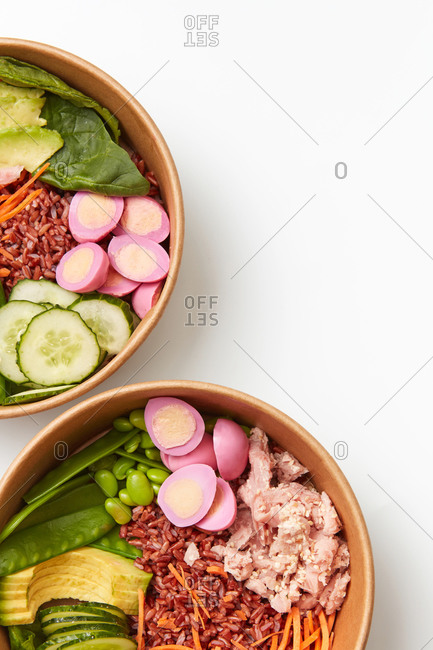 Bowl with healthy organic vegetarian food. Buddha bowls with dark rice, eggs, avocado, fresh spinach and cucumber on a light gray background, copy space. Top view. Clean healthy food.
