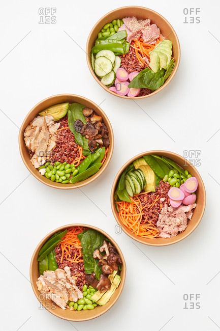 Dinner from healthy food in ceramic bowls with organic natural ingredients dark rice, eggs, avocado, spinach and chicken slices on a light grey background, copy space. Top view. Clean healthy food.