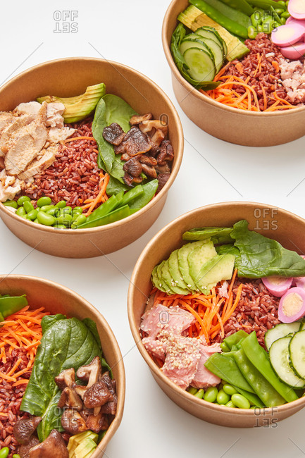 Four close-up ceramic bowls with healthy food from natural ingredients dark rice, eggs, avocado, fresh spinach and chicken slices on a light gray background, copy space. Clean healthy food.