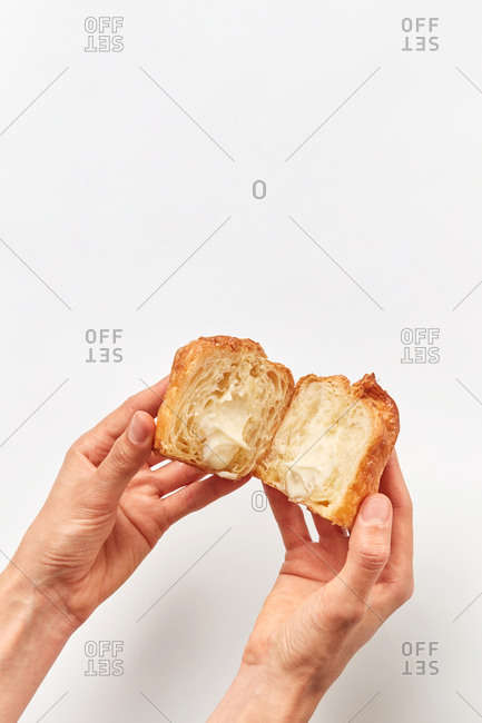 Freshly baked sweet delicious cut bun with white soft milk cream inside in woman's hands above light grey background, copy space. Top view.