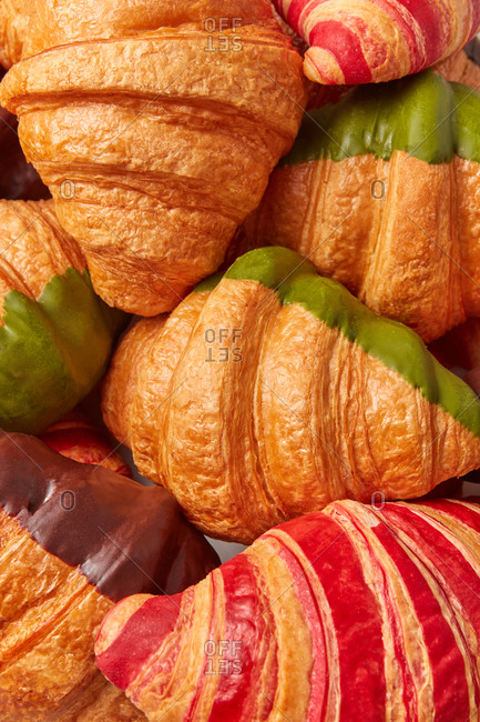 Close up pastry background from freshly baked homemade French croissant with green, chocolate and red jam sweet icing. Top view. Continental breakfast concept.