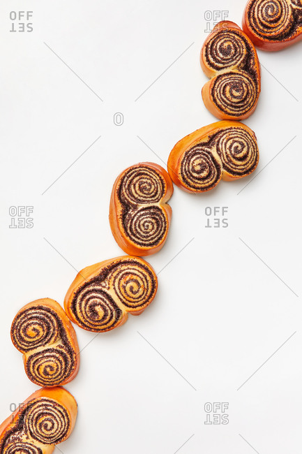 Freshly baked sweet delicious rolled buns with poppy, diagonal bakery pattern on a light grey background, copy space. Flat lay.