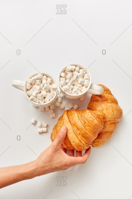 Woman's hand holds freshly baked croissants and two cups of cacao or chocolate drinks with marshmallows on a white background, copy space. Top view.