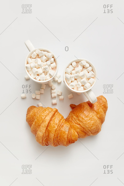 Two freshly baked homemade croissants and ceramic cups of hot cacao or chocolate drinks with marshmallows on a white background, copy space. Top view.