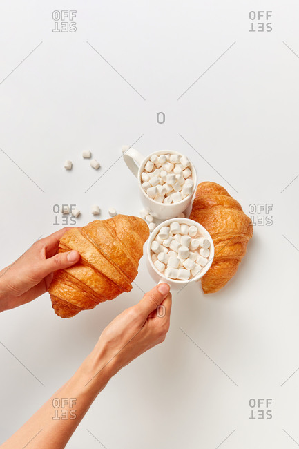Female hands hold freshly baked delicious croissants and cup of hot cacao or chocolate drink with marshmallows above light grey background, copy space. Top view.