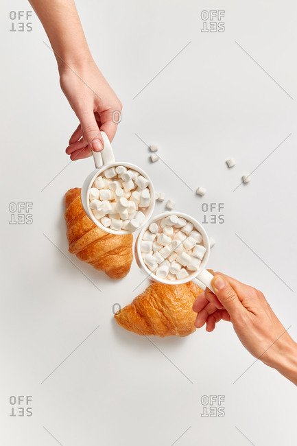 Two woman's hands with ceramic cups of hot chocolate of cacao drinks with marshmallows above light grey background with two freshly baked croissants, copy space. Top view.