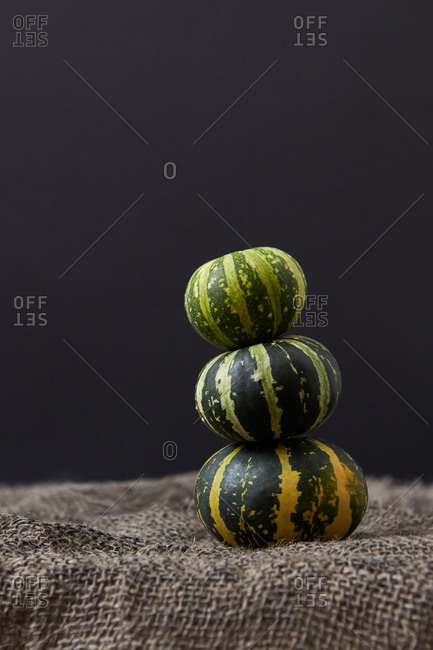 Vegetables balanced stack from freshly picked natural organic pumpkins different size on a canvas textured table against black background, copy space. Vegan concept. Halloween concept.