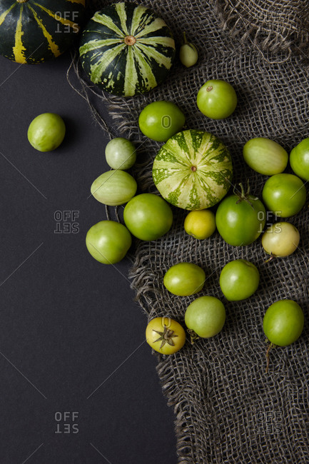 Vegetarian pattern from freshly picked natural organic unripe vegetables pumpkins and tomatoes of green color on canvas textile and black background, copy space. Vegan healthy food concept. Top view.