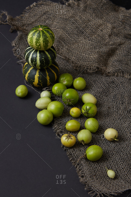 Vegetarian set from homegrown freshly picked organic vegetables pumpkins stack and tomatoes of green color on canvas textile and black background, copy space. Vegan healthy food concept. Top view.