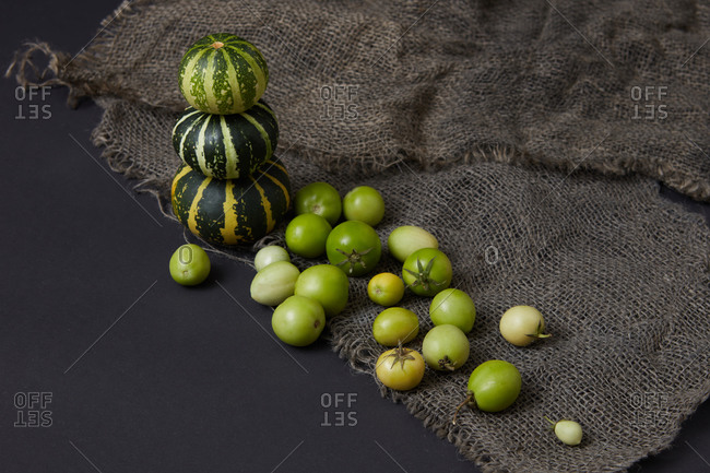 Harvest from homegrown freshly picked organic natural vegetables pumpkins pyramid and tomatoes of green color on canvas textile and black background, copy space. Vegan healthy food concept. Top view.