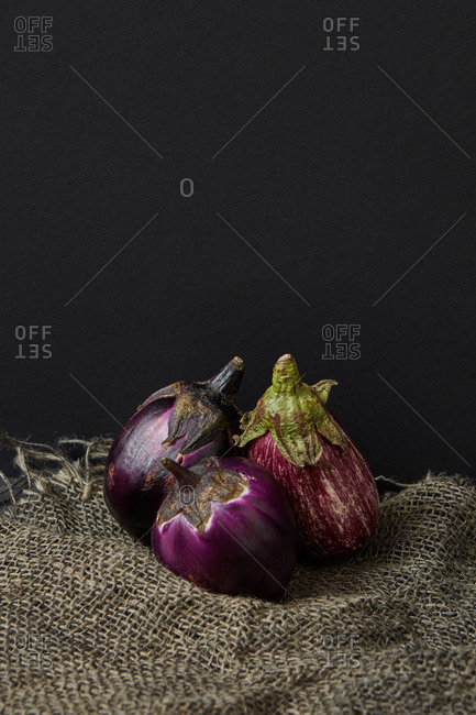 Vegan harvest from freshly picked natural organic vegetables ripe eggplant on canvas towel against black background, copy space. Vegan healthy food concept. Top view.