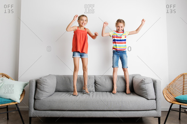 Two happy young girls jumping on sofa at home