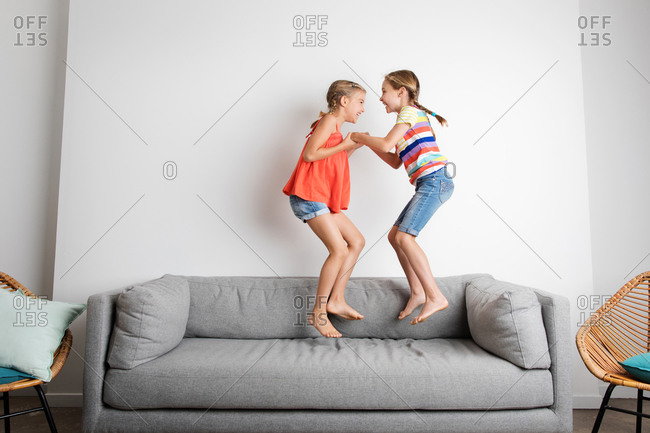 Two laughing little girls jumping on sofa at home