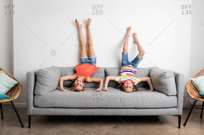 Two happy little girls doing headstands on sofa at home