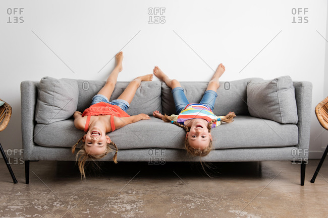 Two smiling little girls lying upside down on sofa at home