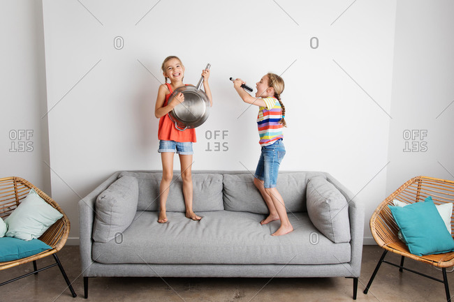 Two happy little girls pretending to sing and play music on sofa
