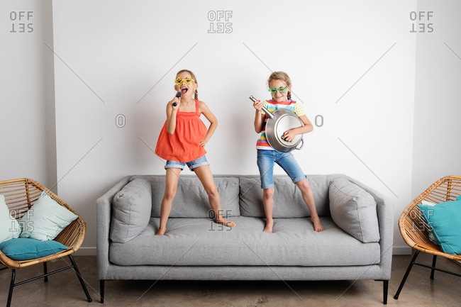 Two funny young girls pretending to sing and play music on couch
