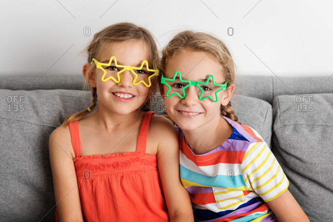 Portrait of smiling young girls wearing star-shaped glasses