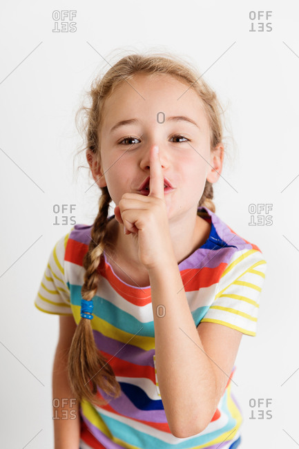Young girl hushing with finger on mouth