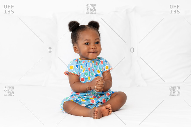 Smiling baby girl with hair buns sitting on bed