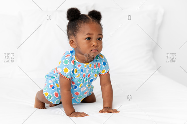 Baby girl with hair buns crawling on bed