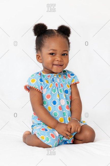 Smiling baby girl with hair buns sitting on bed looking at camera