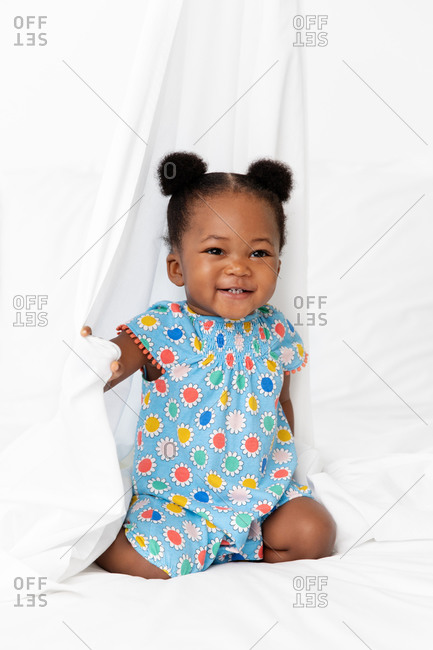 Happy baby girl with hair buns playing with white sheet