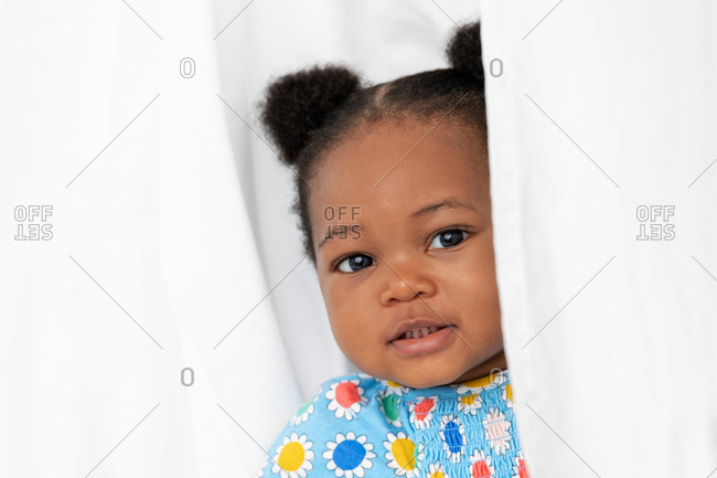 Cute baby girl with hair buns peeking behind white sheet