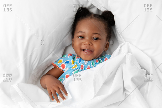 Happy baby girl with hair buns lying on white bed