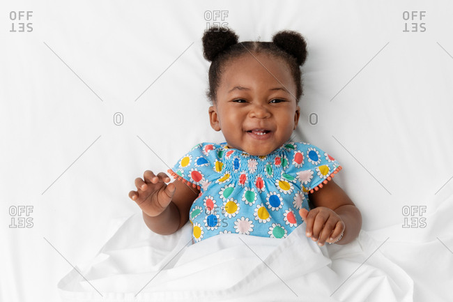 Laughing baby girl with hair buns lying on white bed