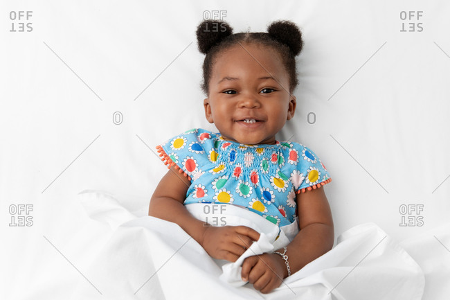 Smiling baby girl with cute hairstyle lying on white bed