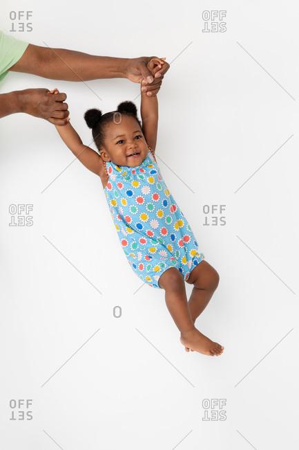 Smiling baby girl swinging against white wall