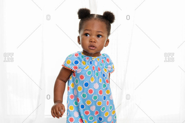 Portrait of toddler girl with hair buns in front of curtains