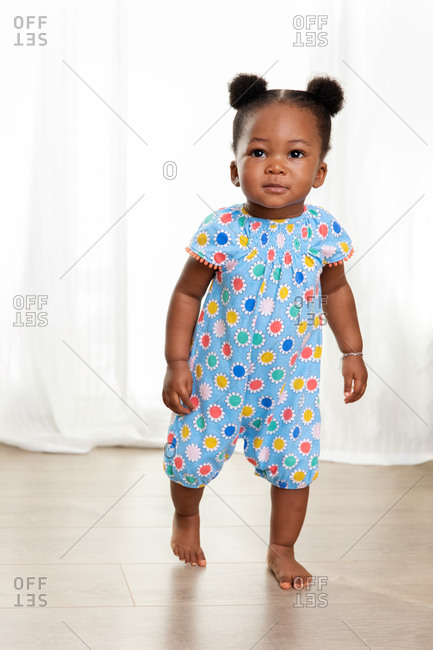 Cute toddler girl with hair buns walking on wooden floor