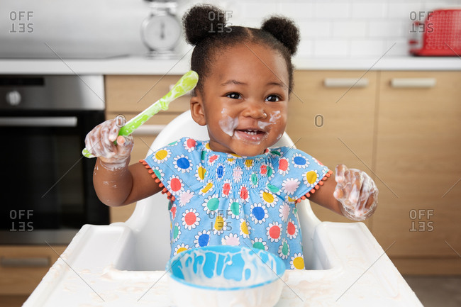 Happy baby girl with messy face eating yogurt with spoon in high chair