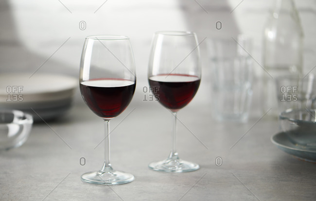 Two glasses of red wine on kitchen countertop