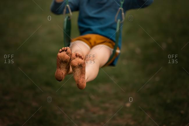 Close up shot of little boy's dirty feet on swing