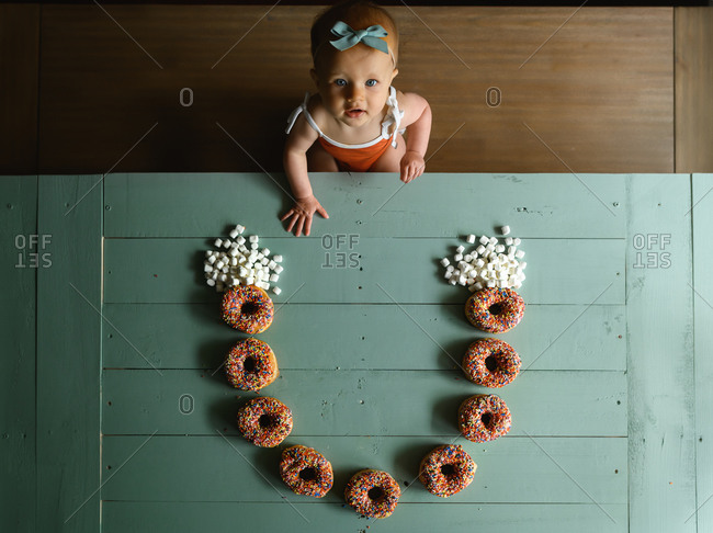 Overhead shot of little girl looking at camera with a rainbow made from doughnuts on table in front of her