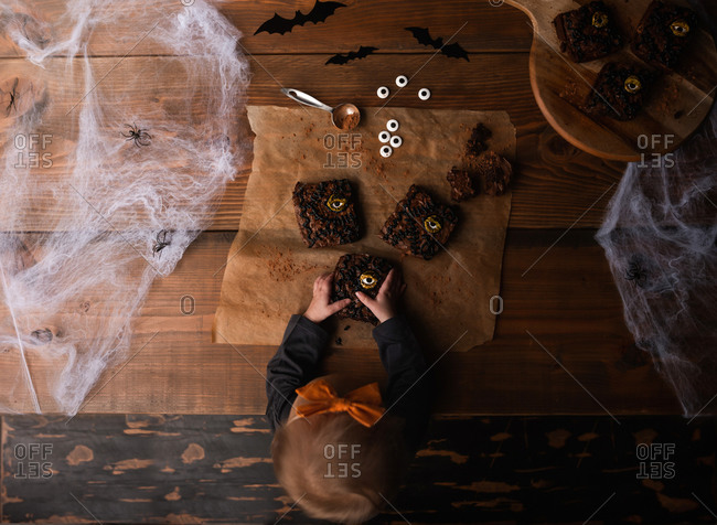 Flat lay of little girl holding Halloween brownies