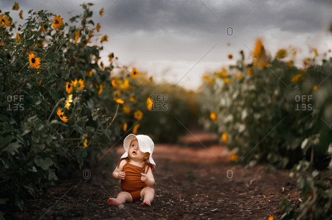 Little girl sitting among little sunflowers with a dirty face